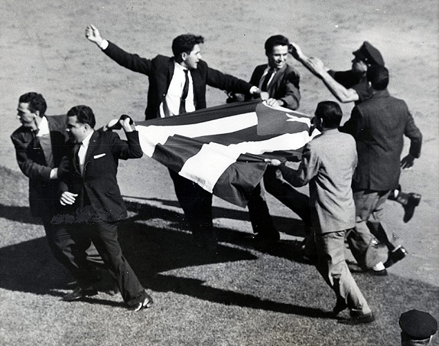 Flag-waving anti-Castro Cuban demonstrators are rushed off the field during a Mets-Braves baseball game