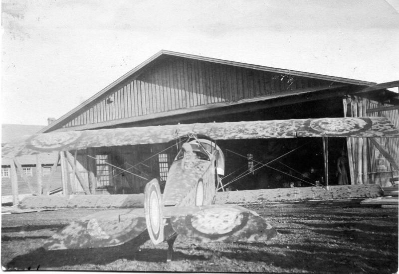Замаскированный самолет стоит перед деревянным ангаром с большими окнами. 1917.jpg