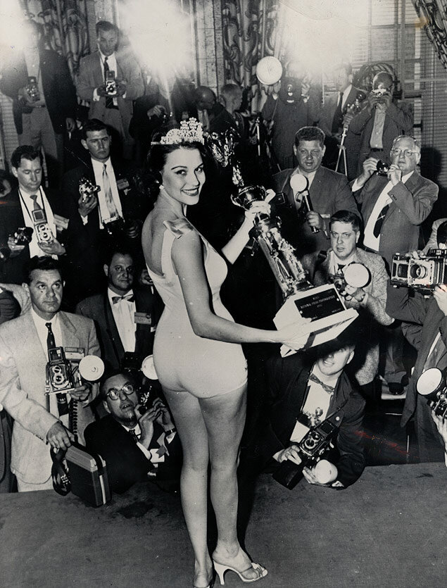 Carole Michelson poses before NPPA members after being chosen Miss National Press Photographer of 1957