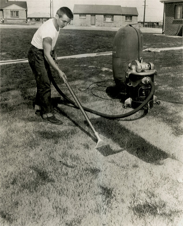 Russell Lloyd, Jr., of Denver, Colorado, vacuums dust from the grass of his front lawn following a massive dust storm