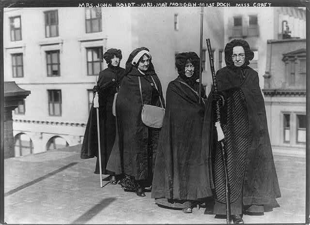 """Mrs. John Boldt, Mrs. May Morgan, Miss Dock and Miss Craft [holding """"Votes for Women"""" staff]"""