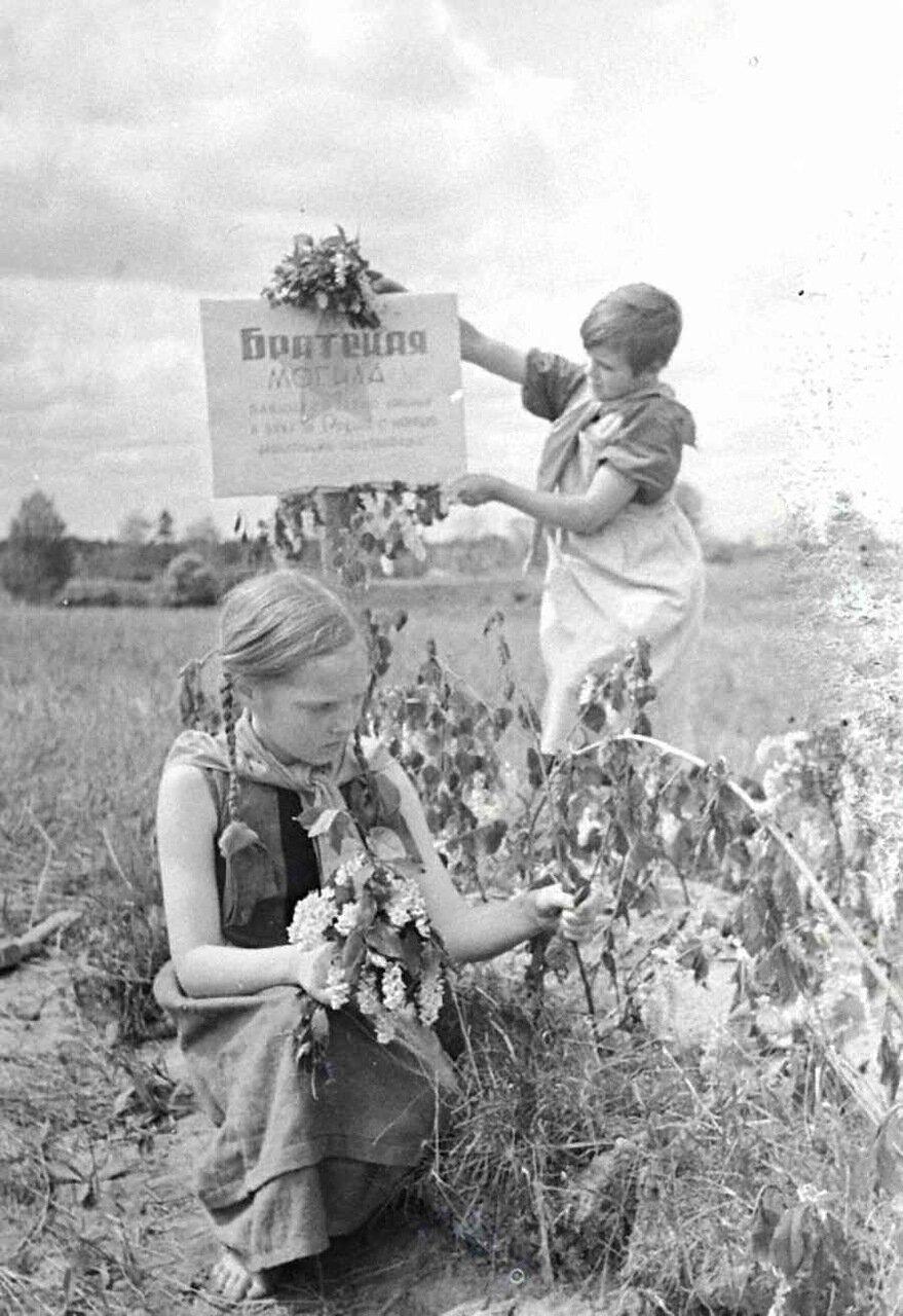 Пионерки Таня Кострова и Маня Михеева ухаживают за братской могилой в освобожденном от немцев селе 1942