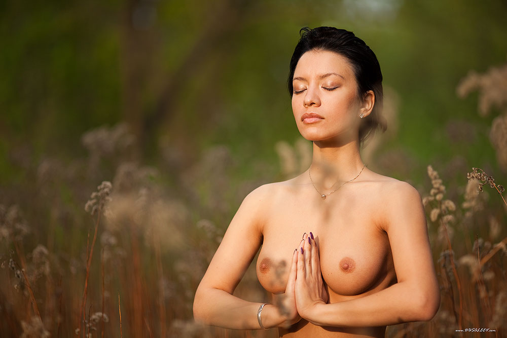 Young nude woman does yoga