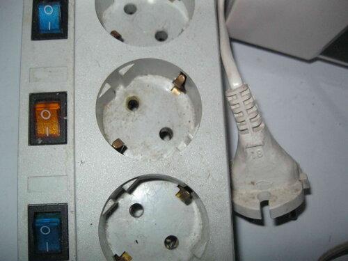 Фото 11. С диагностической целью от сетевого фильтра отключены все электроприборы. Обратите внимание на верхнее отверстие гнезда, расположенного в центре фото - оно имеет следы перегрева из-за превышения допустимой нагрузки.