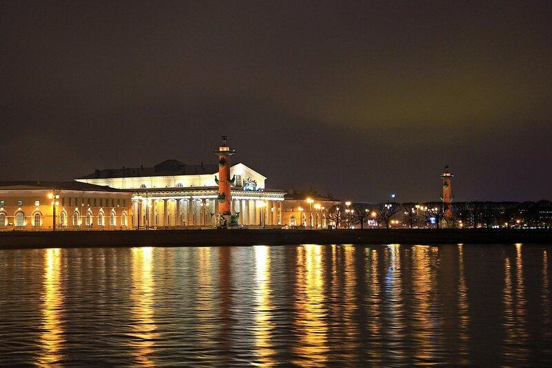 Здание Биржи и Ростральные колонны на стрелке Васильевского острова в Санкт-Петербурге и торажение огней подсветки в воде реки Невы.