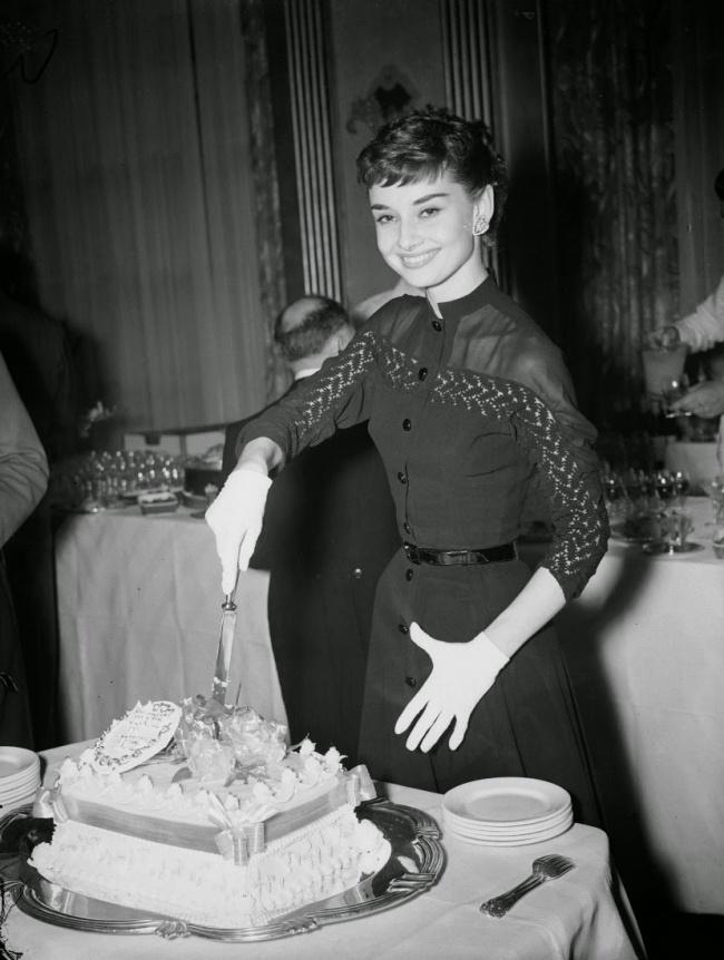 Одри Хепберн позирует с тортом во время коктейльной вечеринки в ее честь. 1953 г.