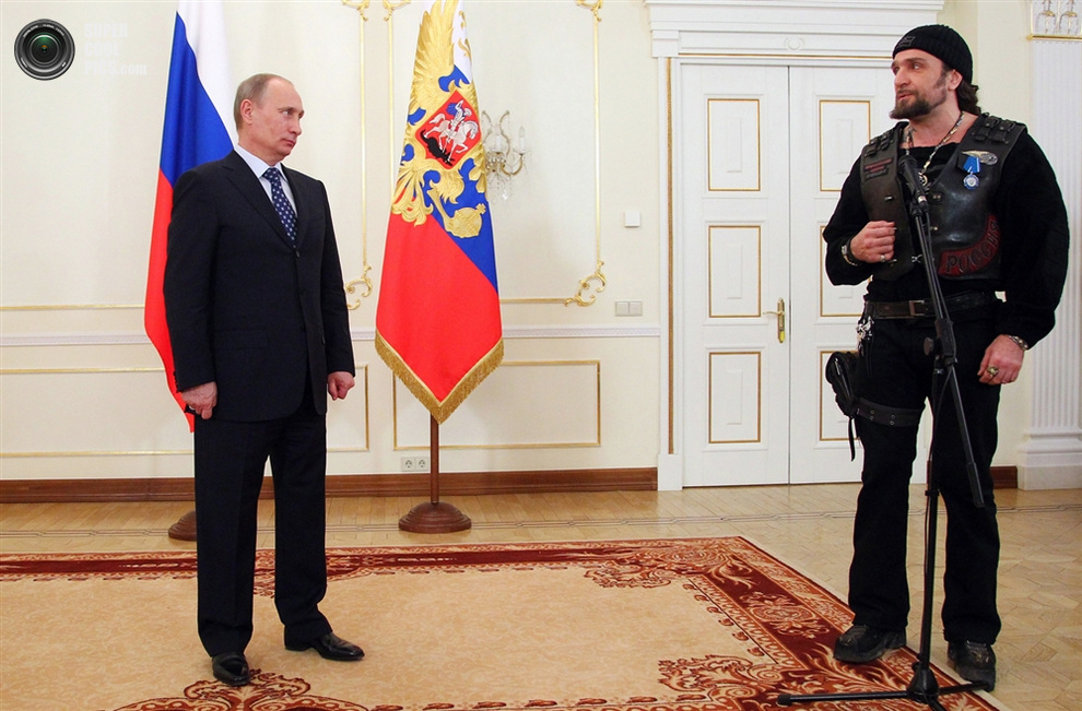 Владимир Путин оценивающе смотрит на «Хирурга» с серебряным орденом на старой байкерской жилетке, Ново-Огарёво, Россия