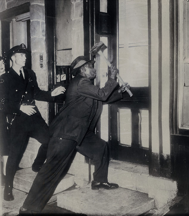 Police detective Thomas Murray wields a sledge hammer to break in a door during city-wide police raids on dope traffickers in the biggest mass raid in Philadelphia, Pennsylvania.jpg
