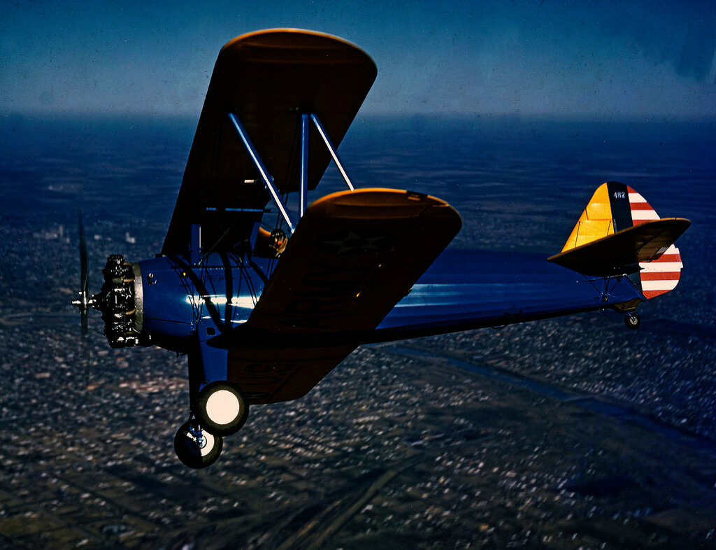 Low left side aerial view of U.S. Army Air Forces Stearman [Boeing-Stearman] PT-17 Kaydet (Model A75N1) in flight, 1941.
