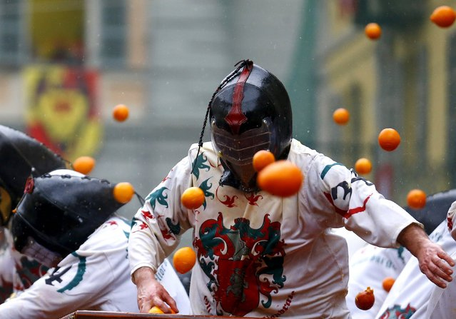 Members of rival teams fight with oranges during an annual carnival battle in the northern Italian t