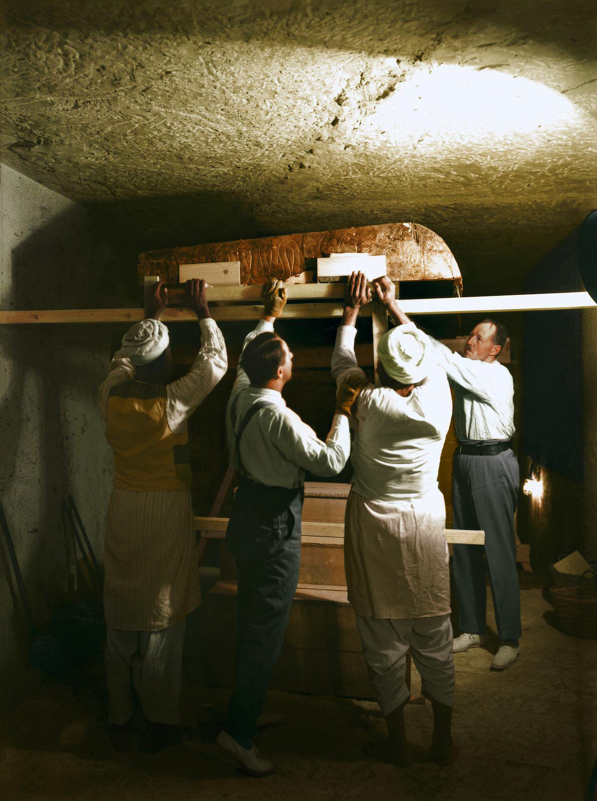 Картер, Каллендер и двое египетских рабочих осторожно достают золотой саркофаг в погребальной камере