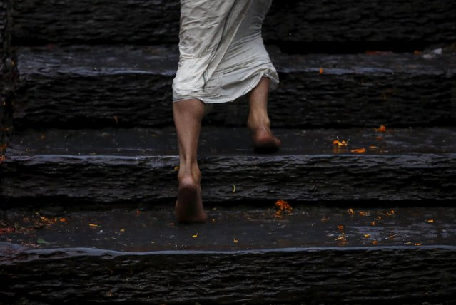 The feet of a devotee is pictured as he offer prayer at the bank of Bagmati River after taking a hol