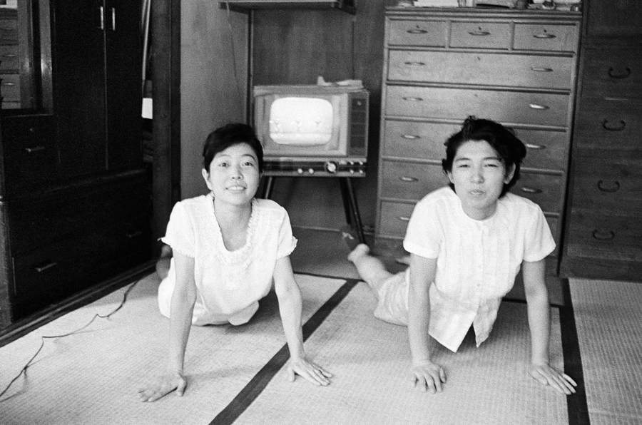 Following a teacher on TV, two young women exercise at home in Tokyo, Japan, on November 5, 1963. Th