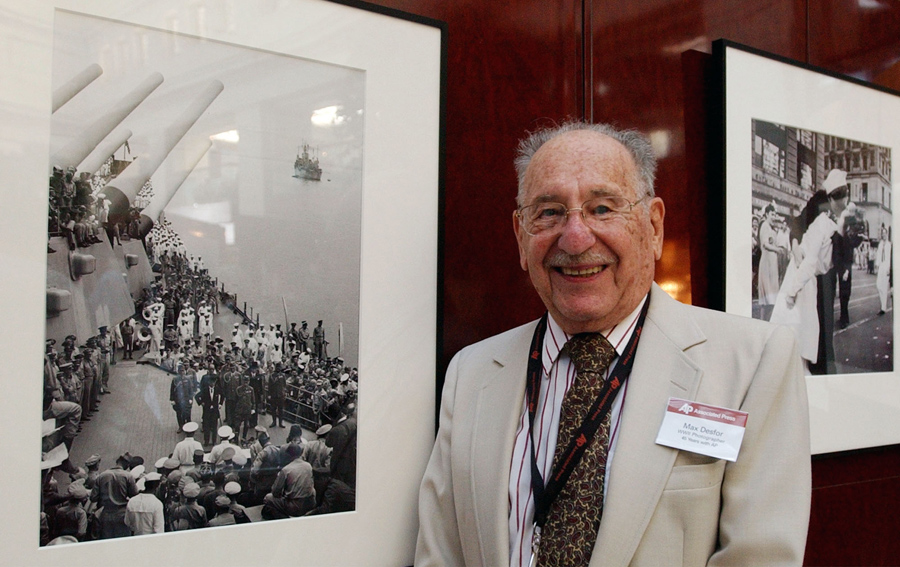 Retired Associated Press photographer Max Desfor stands next to his photograph of Japan's formal