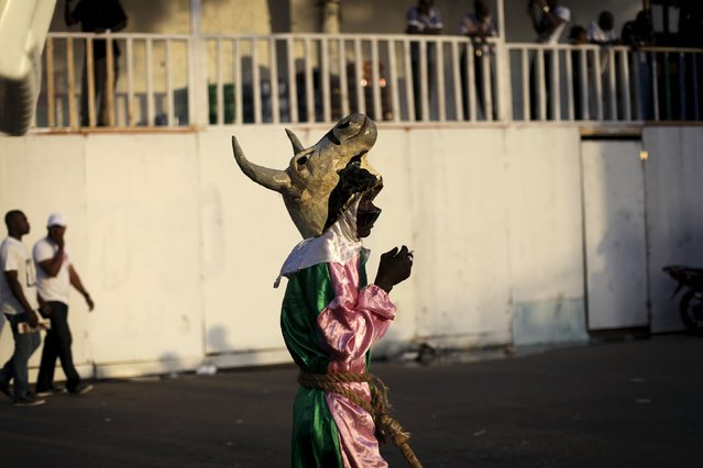 A reveller wearing a papier mache mask representing a cow takes part in the Carnival 2016 parade in