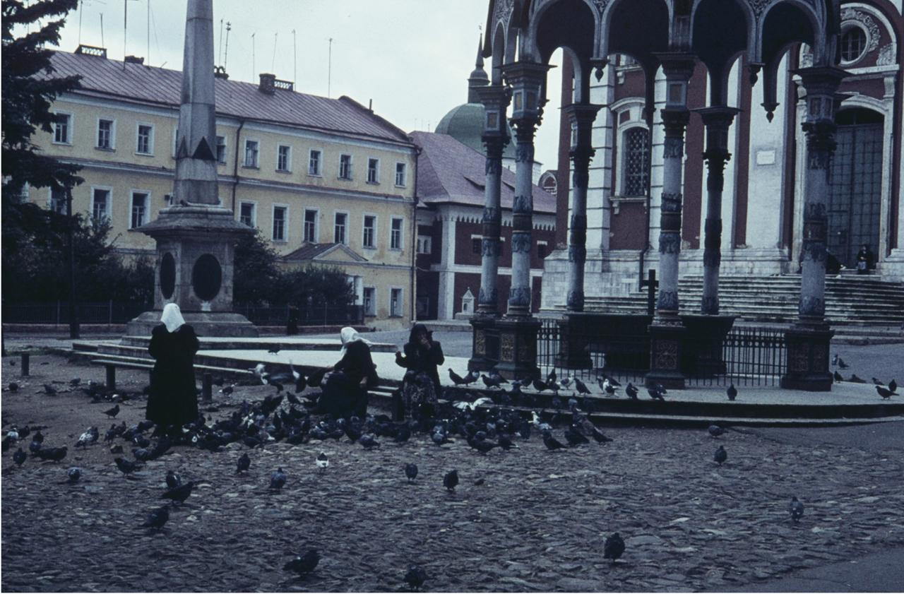 Женщина кормит голубей у фонтана со святой водой