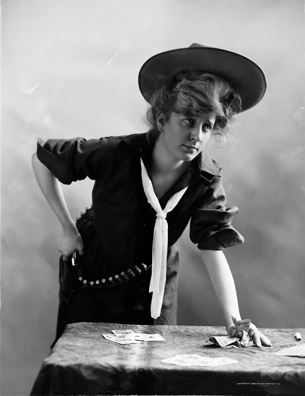 Studio portrait of a woman dressed as a cowgirl. The woman leans one hand on a table with playing cards, other hand on a gun in a holster. 1903.