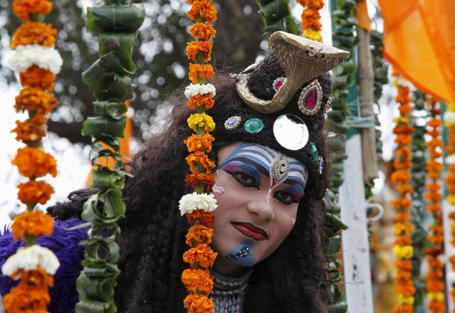 A man dressed as Hindu god Lord Shiva takes part in a religious procession ahead of Maha Shivratri f