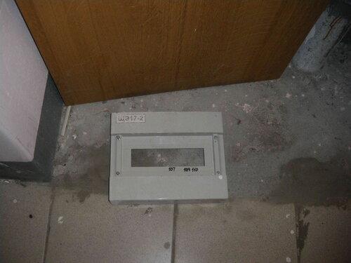 Фото 3. Демонтированная лицевая панель пластикового бокса. В левом верхнем углу панели видна маркировка этажного щита - ЩЭ 17-2, в нижней части чёрным маркером подписано назначение автоматических выключателей (по номерам квартир).