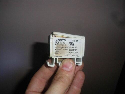 Фото 9. Оплавленный и деформированный нулевой клеммник «Энсто» («Ensto»), извлечённый из этажного щита. Вид сбоку.