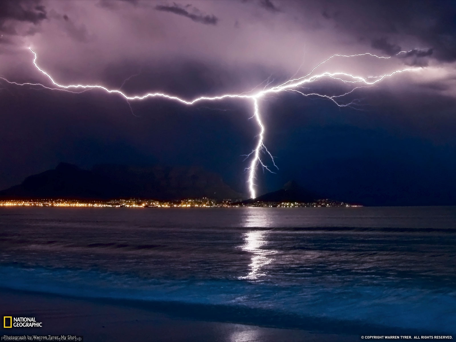 Two separate lightning bolts converge over Table Mountain in Cape Town, South Africa, with an amazing display of natural electricity.