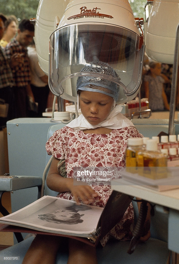 1959 A young woman eyes an old beauty magazine as she sits under a dryer, Moscow by B. Anthony Stewart.jpg