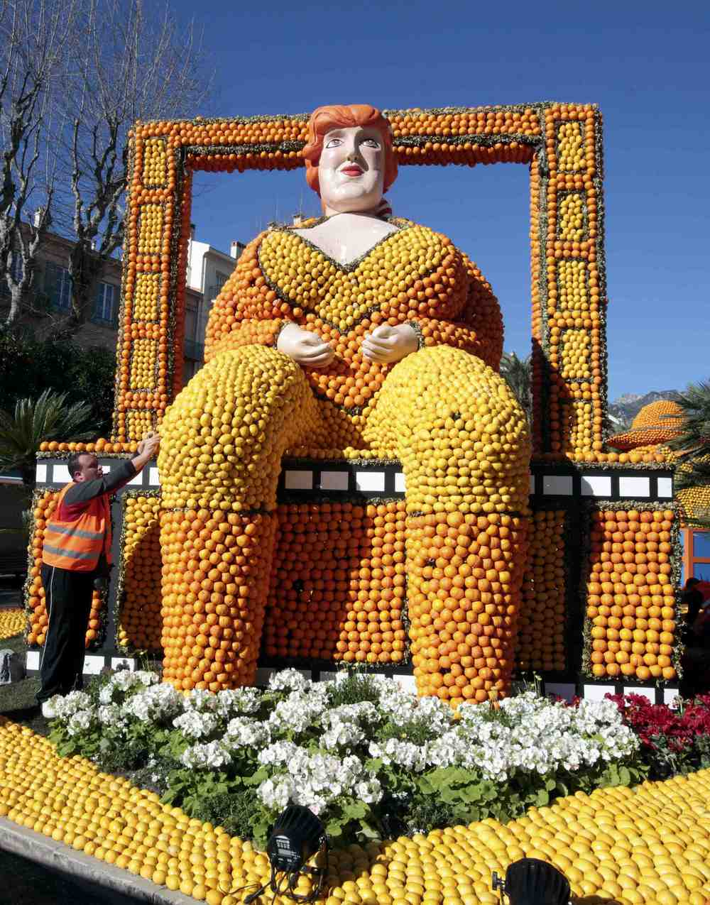 A worker puts the final touch to a replica of a giant woman made with lemons and oranges which shows a scene of the movie