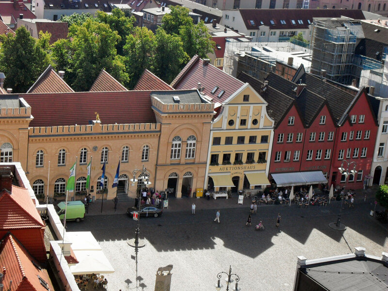 Рыночная площадь внизу Собора (ранее упомянутый лев в нижней части снимка). Здание с позолоченной фигуркой всадника (гербовый знак Шверина) — Ратуша