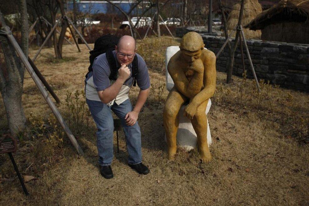 Турист позирует для фото рядом с юмористической копией скульптуры Огюста Родена «Мыслитель».