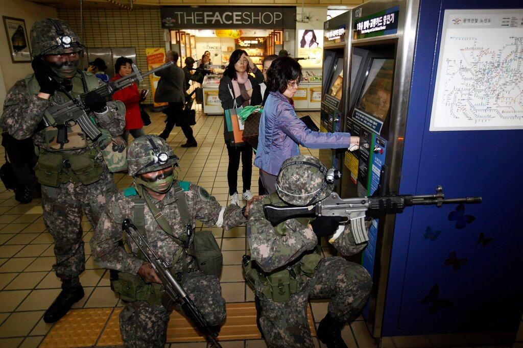 A woman uses a ticket vending machine as South Korean soldiers take part in an anti-terror and security drill at a subway station in Seoul