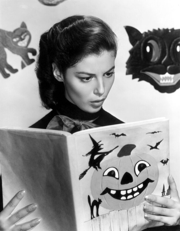 circa 1960: Promotional photo of Italian-born actor Pier Angeli (1932-1971) reading a book for Halloween with black cat decorations in the background.