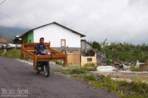 индонезиец на мотоцикле везет двуспальную кровать