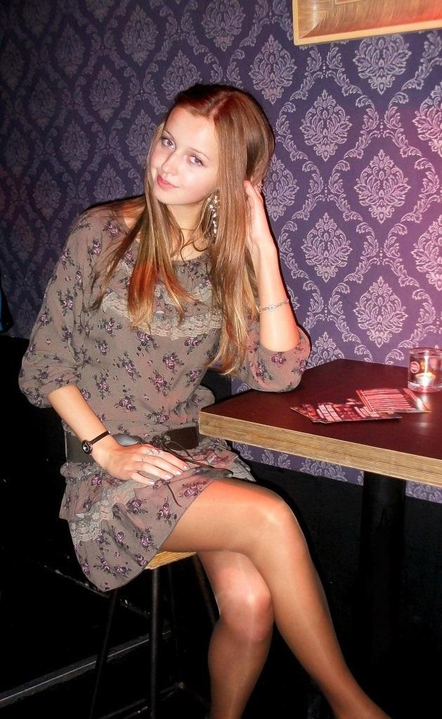 Блондика в кафе за столиком в платье