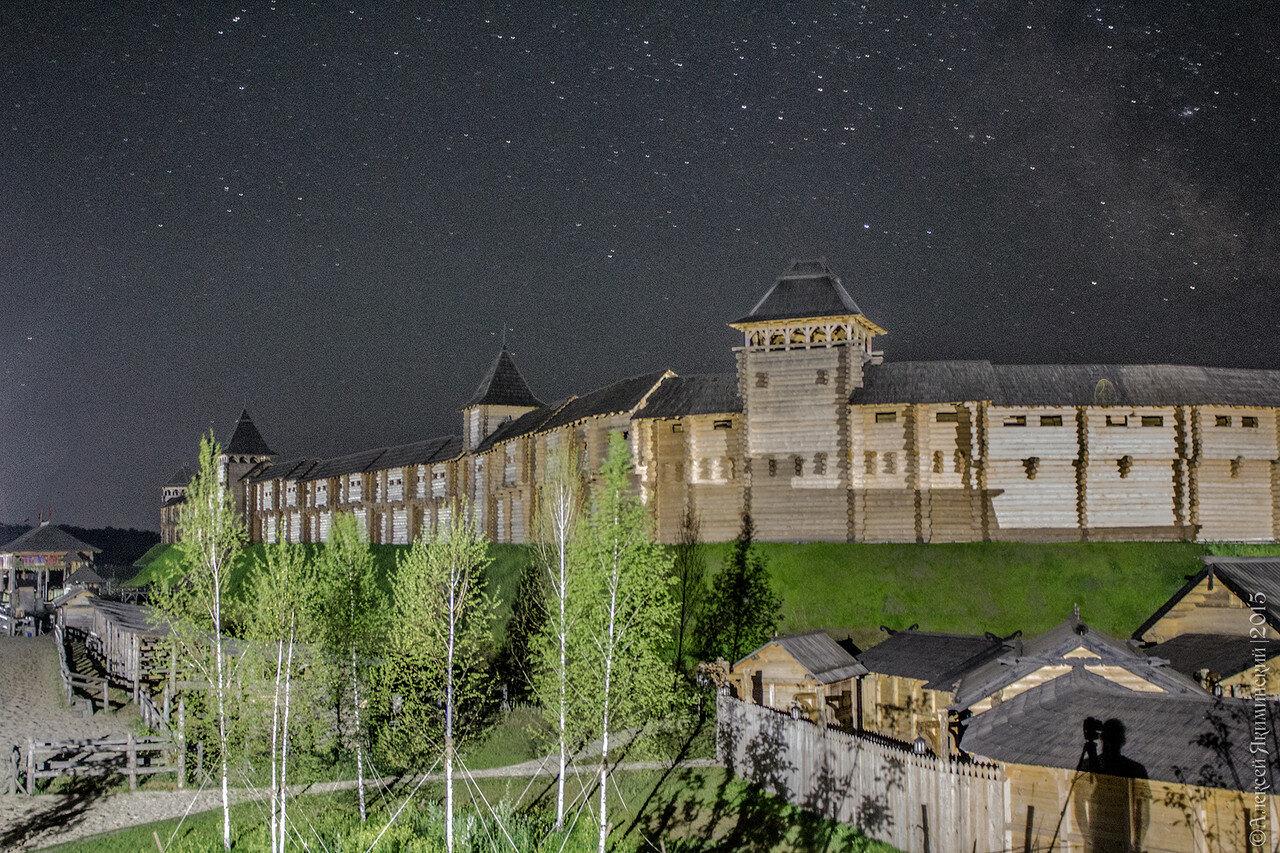 Ночное фото в Древнем Киеве в Парке Киевская Русь. Фотограф со штативом отбрасывает тень на постройки