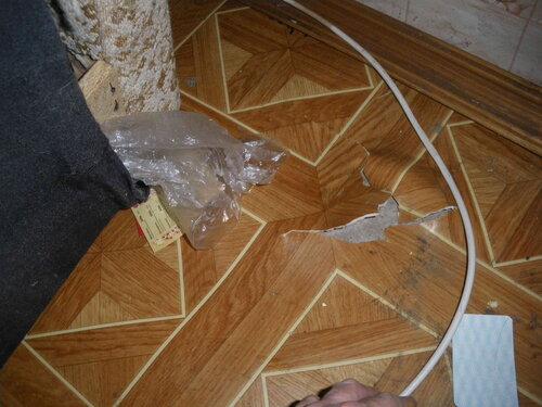 Фото 3. Линолеум был повреждён (ещё до визита электрика нашей аварийной службы) из-за частых перемещений дивана при несоблюдении мер предосторожности. За диваном проложен антенный (телевизионный) кабель.