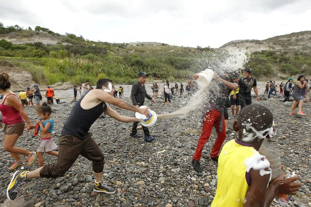 Revellers celebrate with water at the Chota river during a carnival festivity in Coangue, February 8
