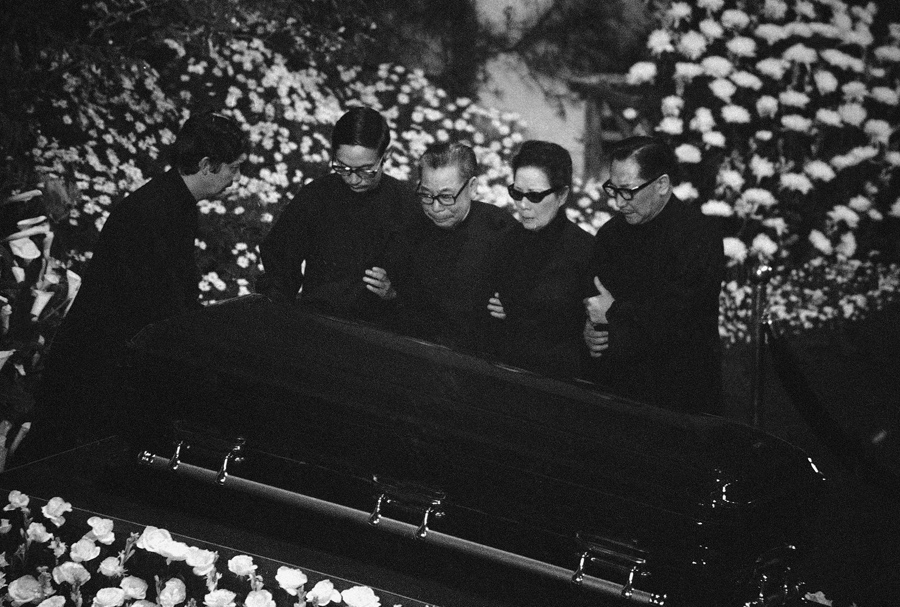 Members of the family of Nationalist Chinese leader Chiang Kai-Shek stand beside his coffin at it is