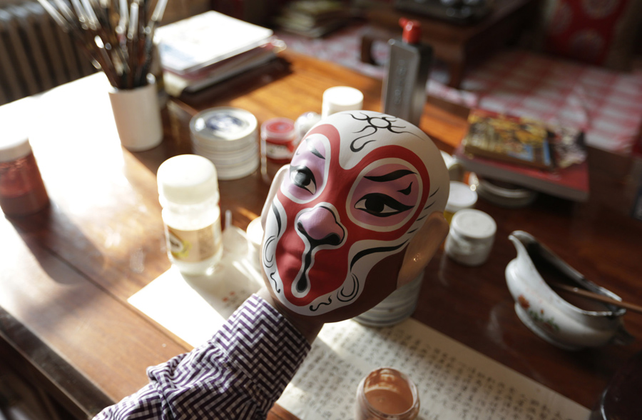 Folk artist Zhao Yongqi checks a monkey mask after painting, at his studio, in Beijing on January 29