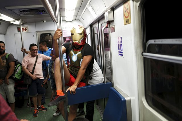 "A passenger with a superhero mask plays inside a subway train during the ""No Pants Subway Ride"" in M"
