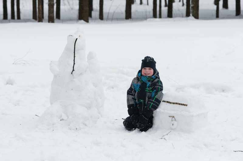 child enjoys the winter and playing with snow