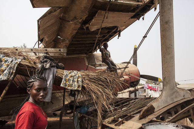 A woman walks under the wing of a plane wreckage being used as housing in M'Poko Internally Dis