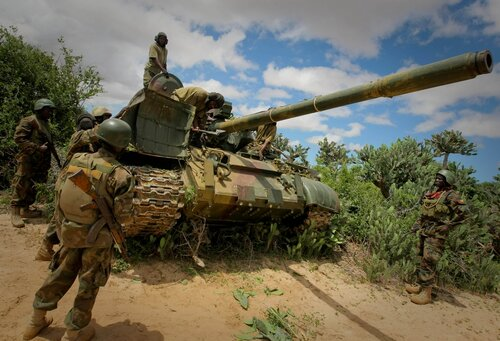 SOMALIA, Afgoye: In a photograph released by the African Union-United Nations Information Support Team 24 May, Ugandan soldiers serving with the African Union Mission in Somalia (AMISOM) pass through thicket near the outskirts of the town of Afgoye, locat