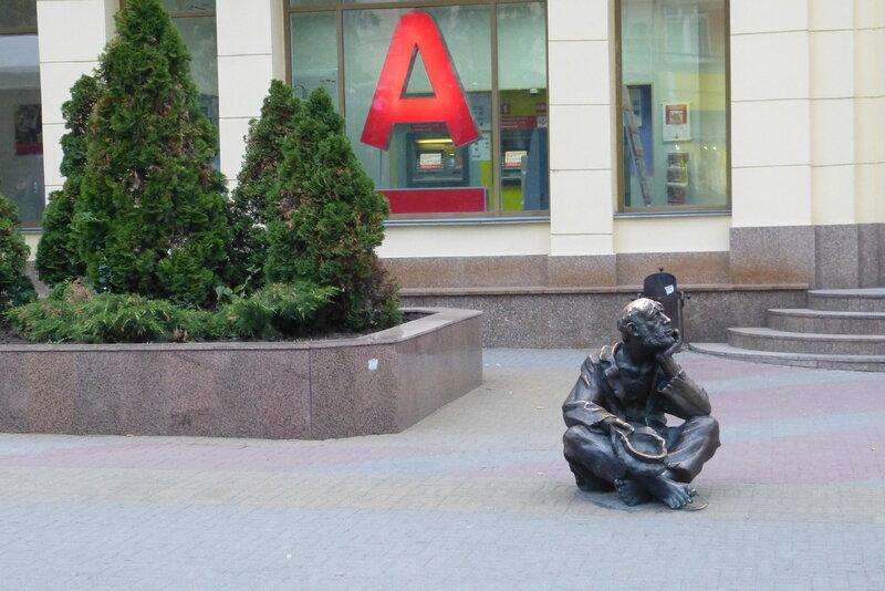 Скульптура нищего у банка