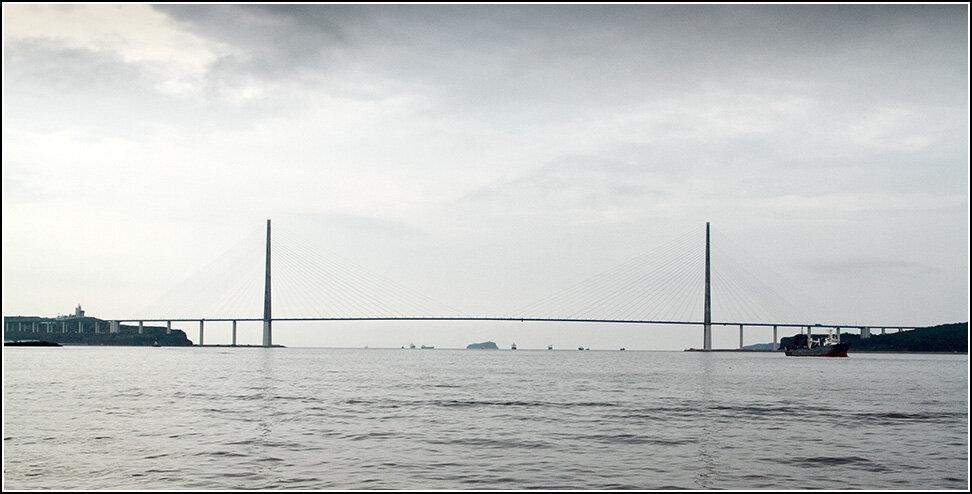 Но осмотр города все же предлагаю осмотреть с его самой дальней части - с острова Русский. На остров перекинут огромный мост, размеры которого, кстати, впечатляют с любой точки, кроме дорожного покрытия. Бюджету мост обошелся в кругленькую сумму, по слухам, около двух миллиардов долларов, что соответствует цене самого большого в мире казино Venetian в Макао.