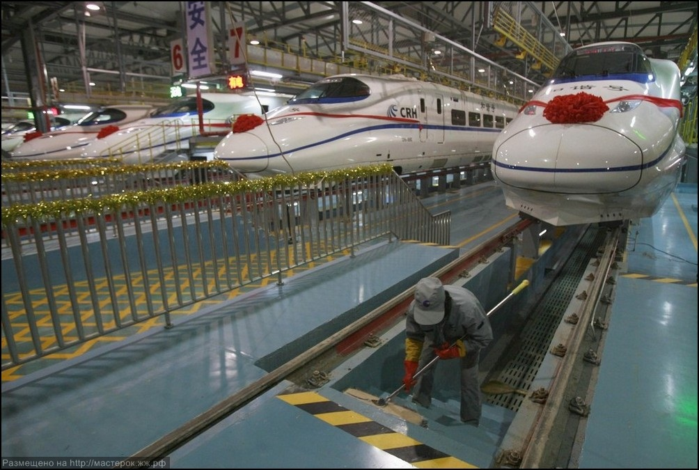 A labourer cleans the stairs beside a China Railway High-speed train preparing for the operation ceremony from Wuhan to Guangzhou in Wuhan