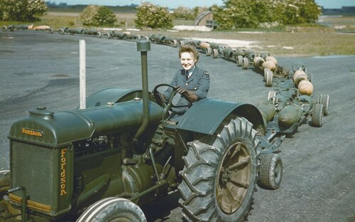 A WAAF tractor driver with a train of full bomb trolleys, RAF Mildenhall 1942.