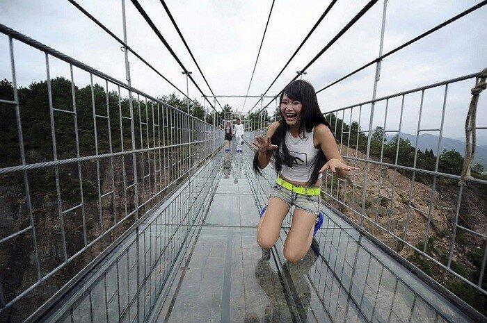 Испуганная туристка во время прохождения по стеклянному мосту.