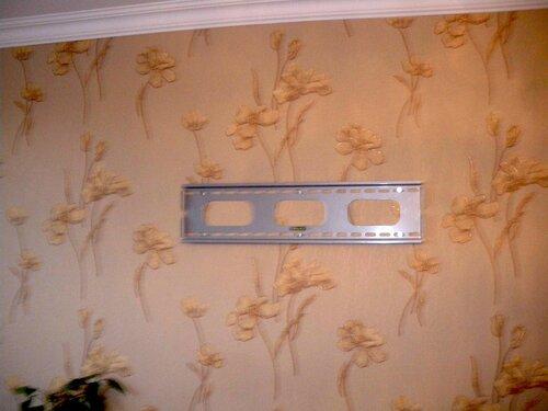 Фото 2. Основание телевизионного кронштейна прикручено к стене с помощью шести саморезов с шестигранной головкой.