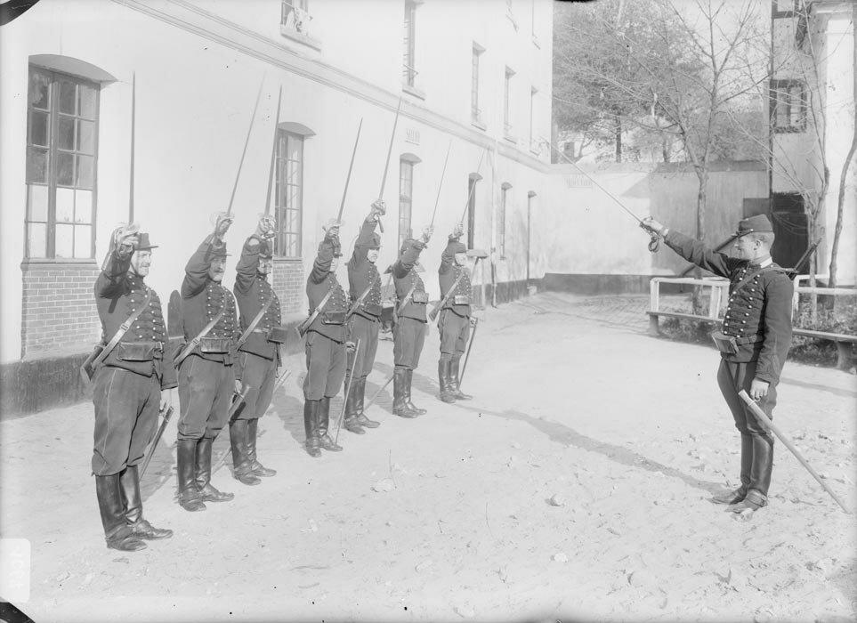 Les cavaliers du 27e regiment de dragons en tenue de campagne levent leurs sabres au clair au signal de l'instructeur dans la cour de la caserne.