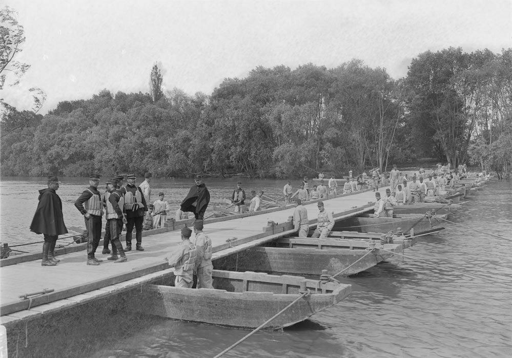 Les pontonniers d'un regiment du genie mettent en place un pont flottant au travers d'une riviere.